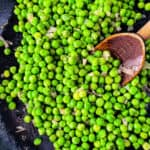 Cooked frozen peas in a skillet with a wooden spoon.