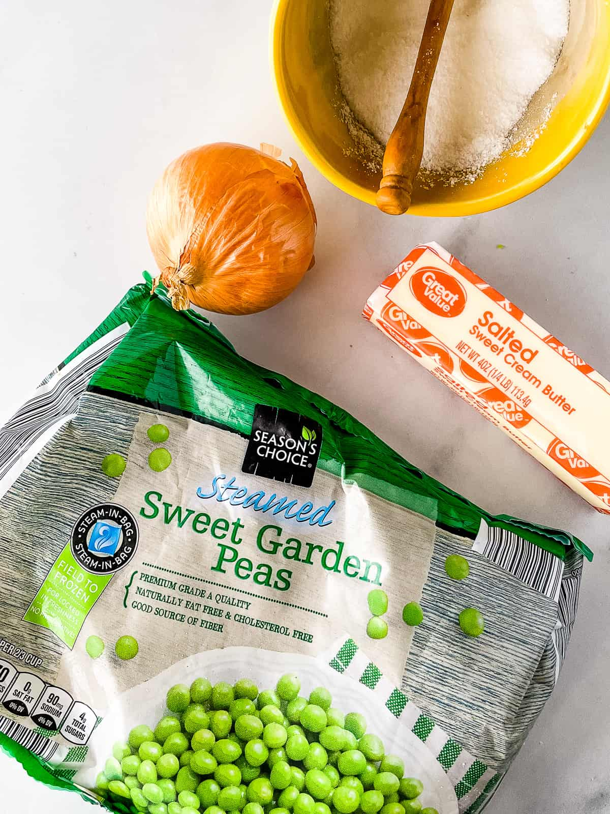 Bag of frozen peas, stick of butter, small onion, and container of salt.