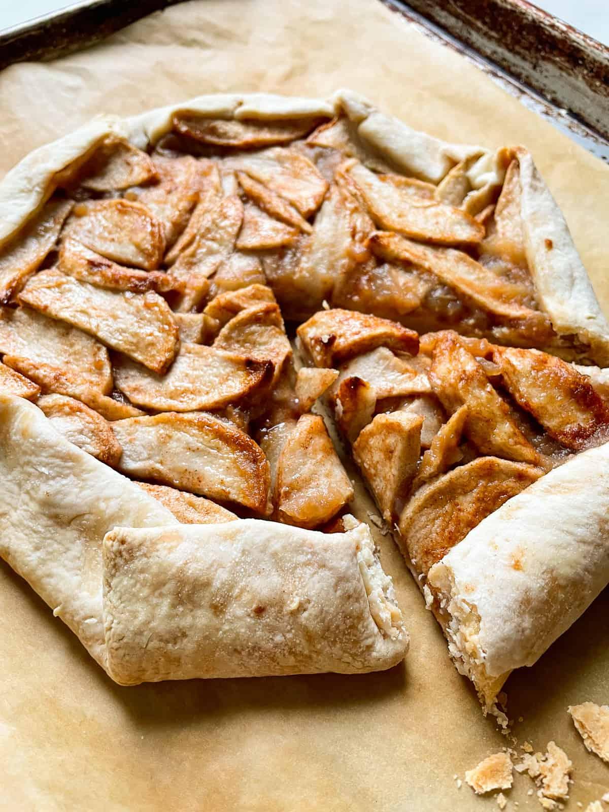 Apple galette sliced on a baking sheet.