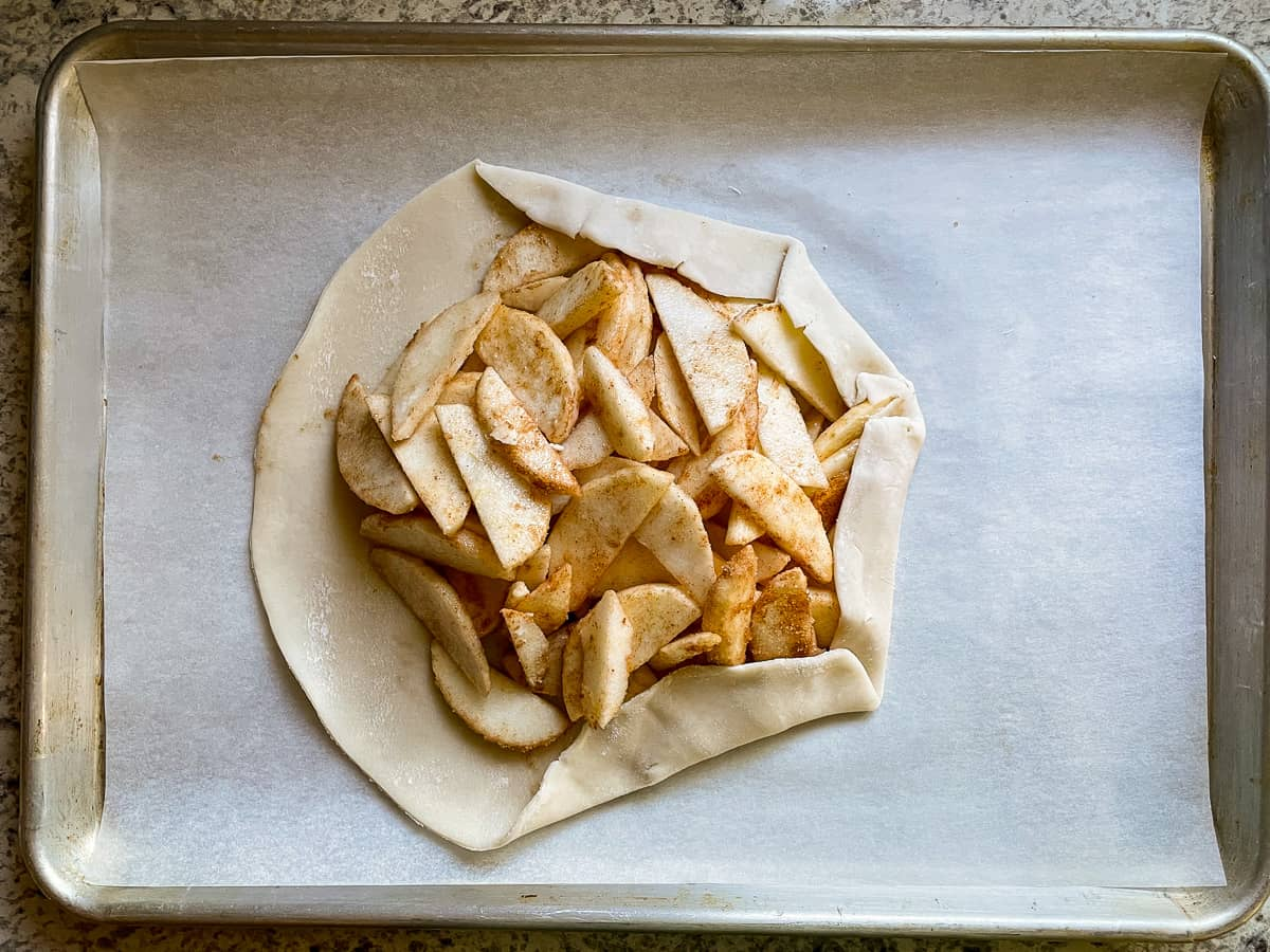 Filled apple galette with pie crust being folded over filling.
