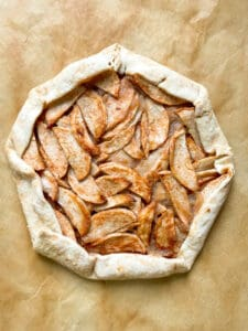 Baked apple galette on brown parchment paper.