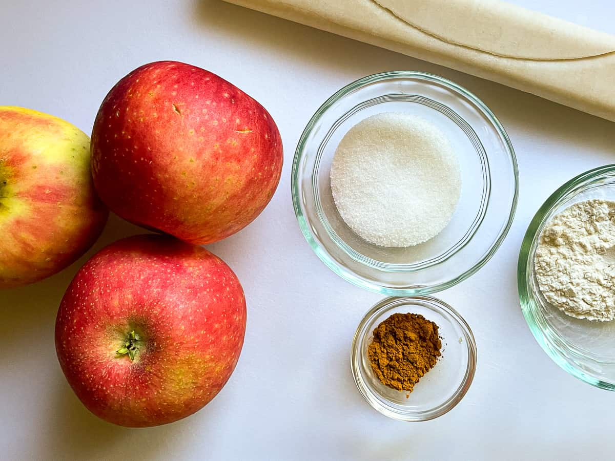 Apples, pie dough, sugar, cinnamon, and flour on a white board.