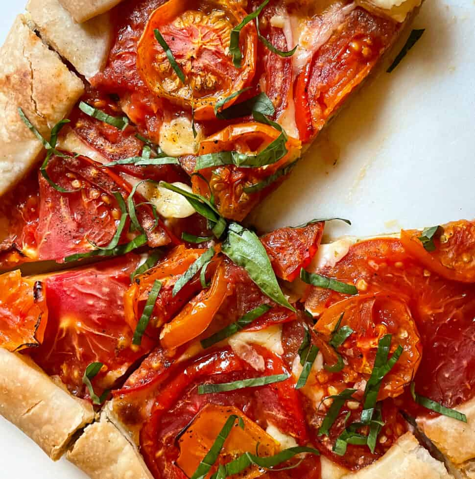 Tomato galette sliced on cutting board.