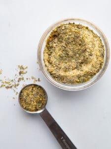 Homemade garlic and herb seasoning in a bowl. Teaspoon of seasoning is beside the bowl.