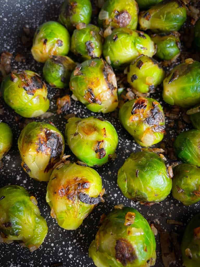 Frozen Brussels sprouts cooked with onions in a pan.