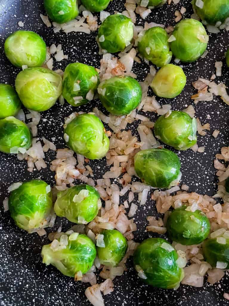 Thawed Brussels sprouts in a skillet with cooked onions.